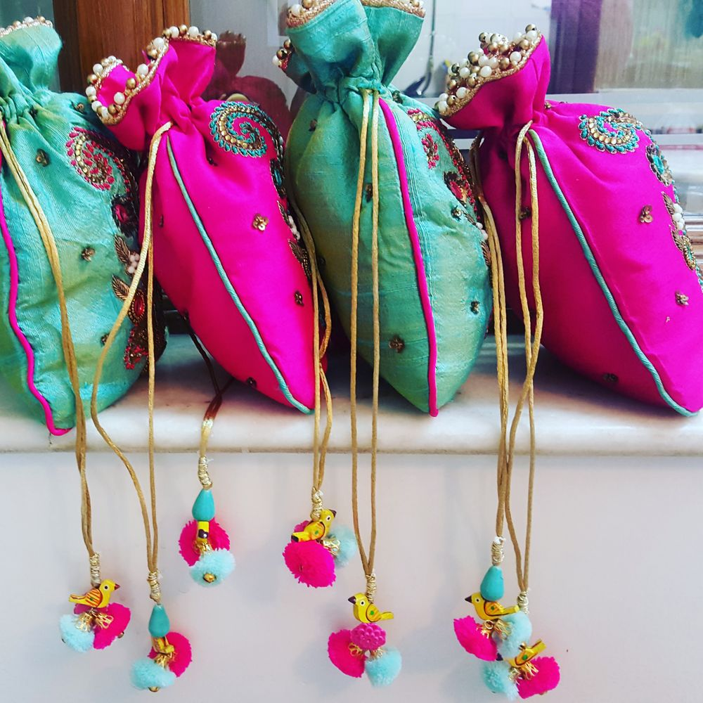 Photo of Colourful potlis with pompoms as mehendi giveaways