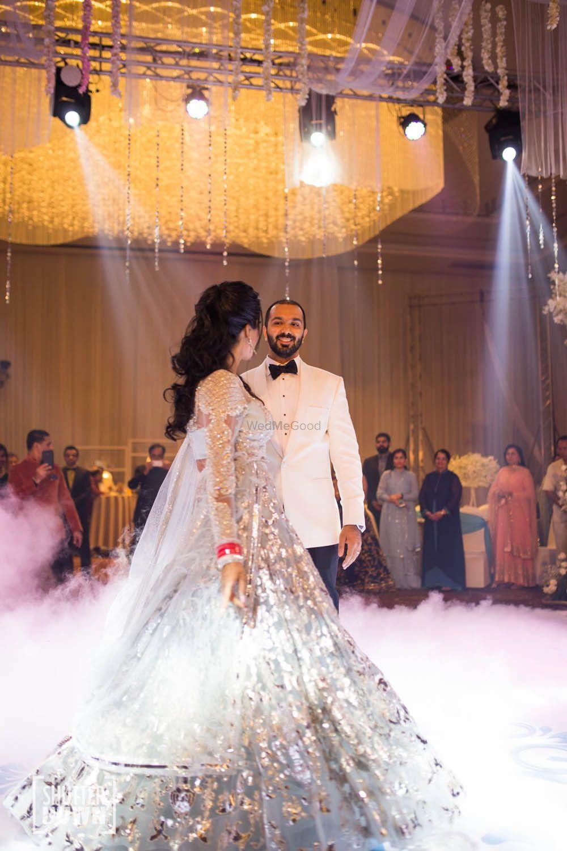 Photo of Couple dancing on stage with bride wearing light grey lehenga