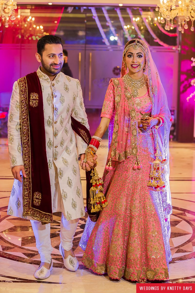 Photo of Bride in coral lehenga with gold sequin work and pink kaleere