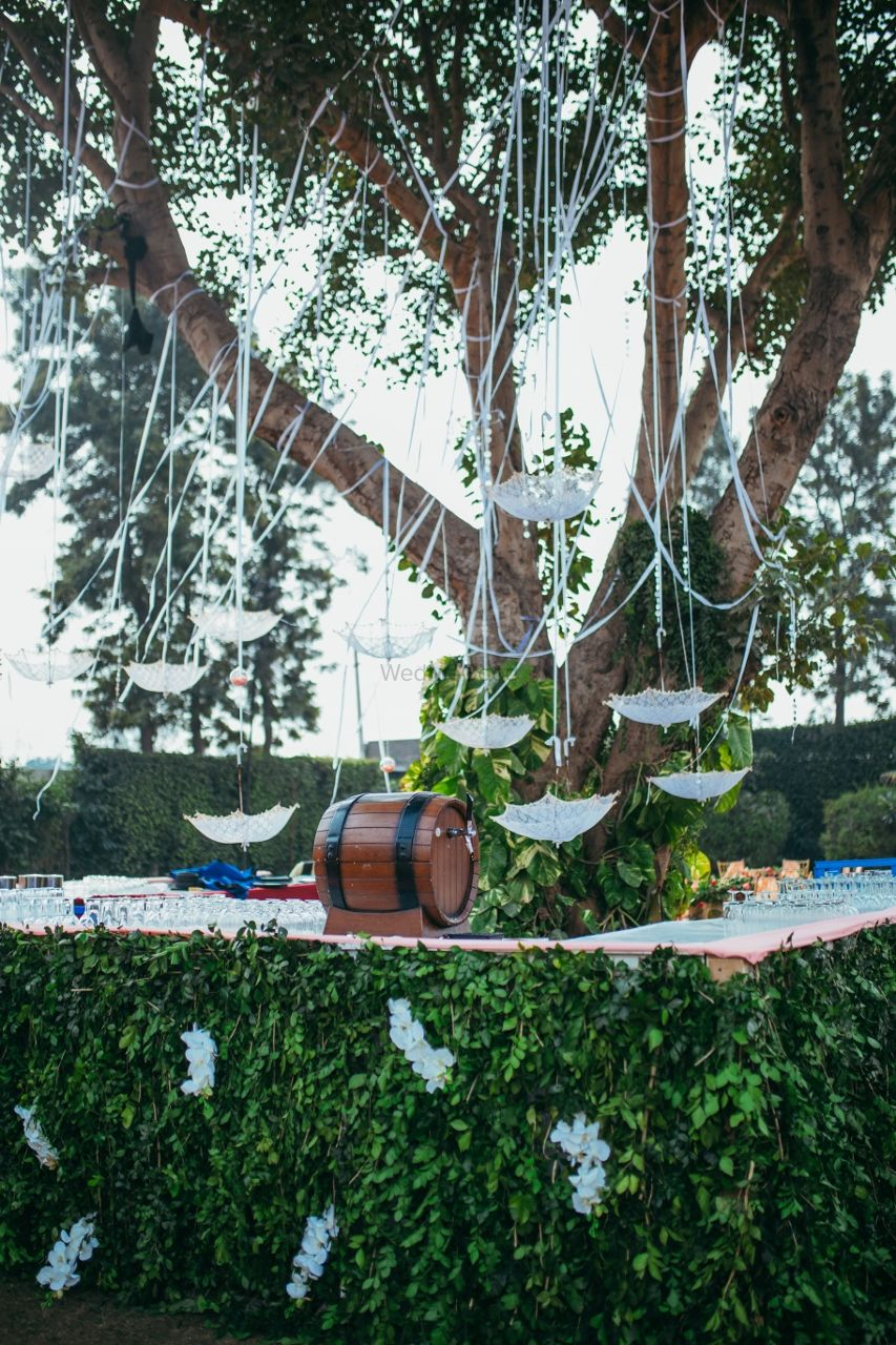 Photo of Backyard decor idea with hanging lace umbrella and beer barrel