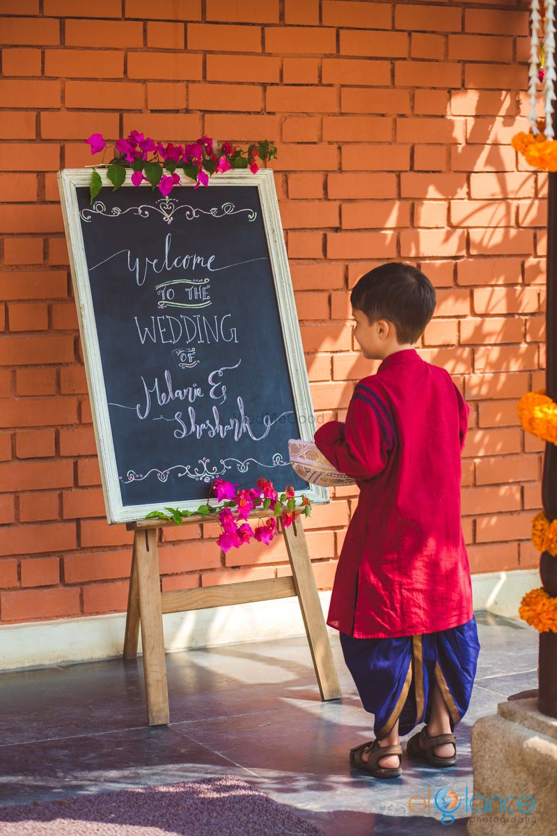 Photo of South Indian wedding entrance decor with personalised blackboard quote