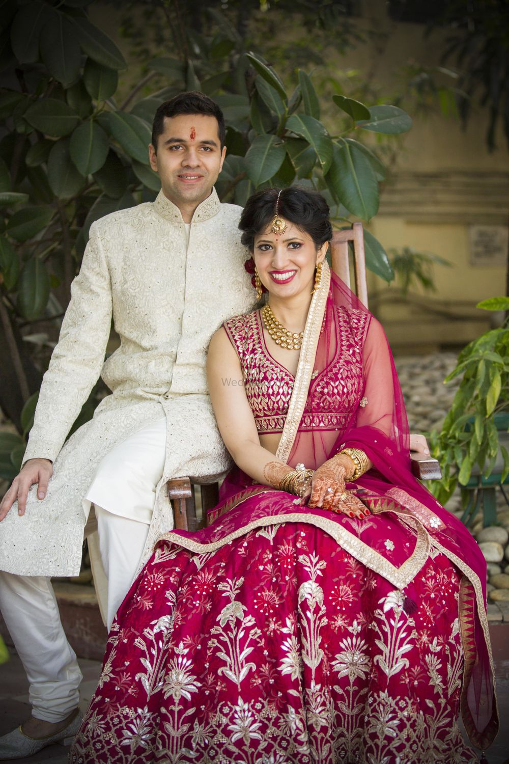 Photo of Coordinated bride and groom with maroon and white outfits
