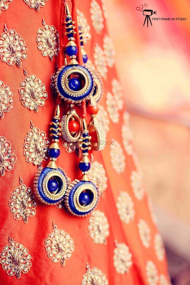 Photo of Orange bridal lehenga with contrasting blue tassels