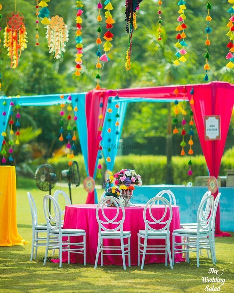 Photo of Colourful mehendi decor with white chairs