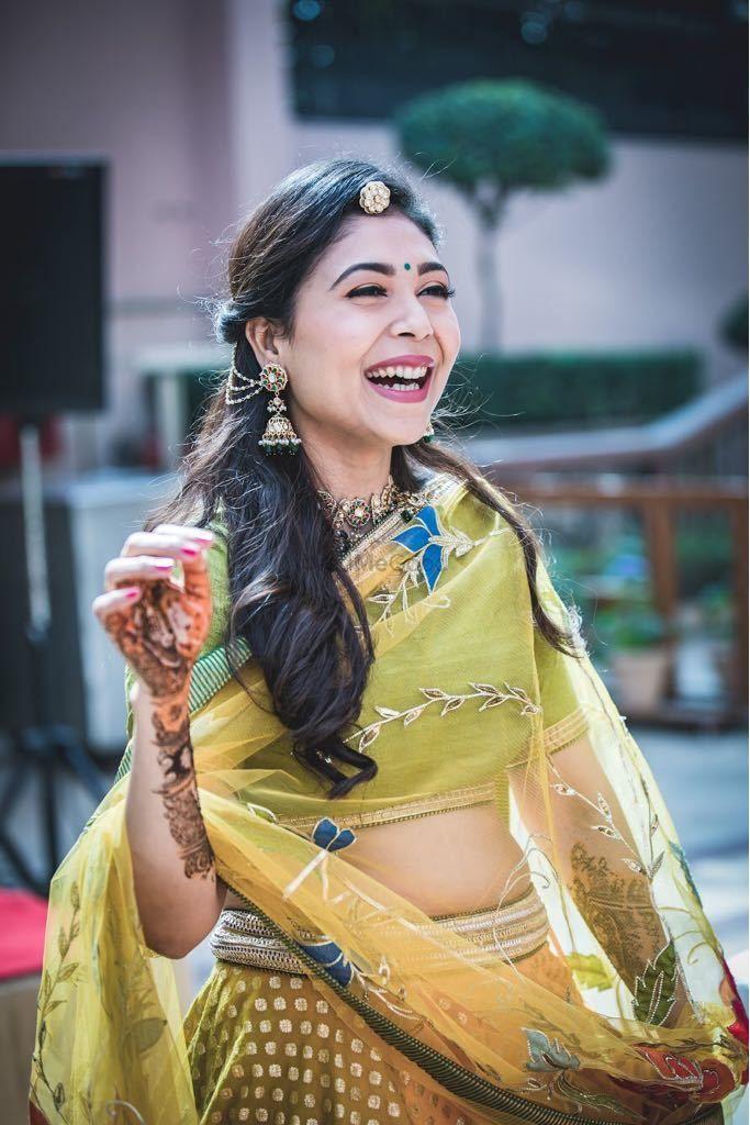 Photo of Happy bride wearing green lehenga on mehendi