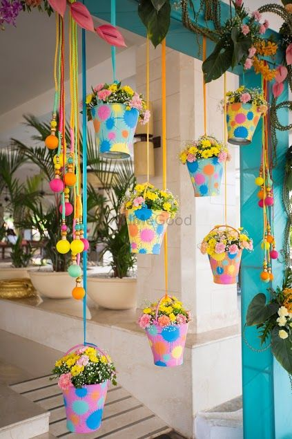 Photo of Colorful hanging buckets with flowers in decor