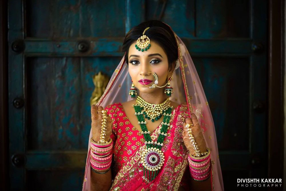 Photo of Pink bridal lehenga with green contrasting jewellery