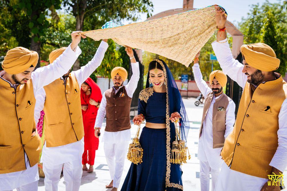 Photo of Bride entering in minimal blue lehenga with groomsmen in yellow