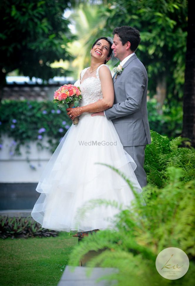 Photo of A Christian couple poses with a bouquet