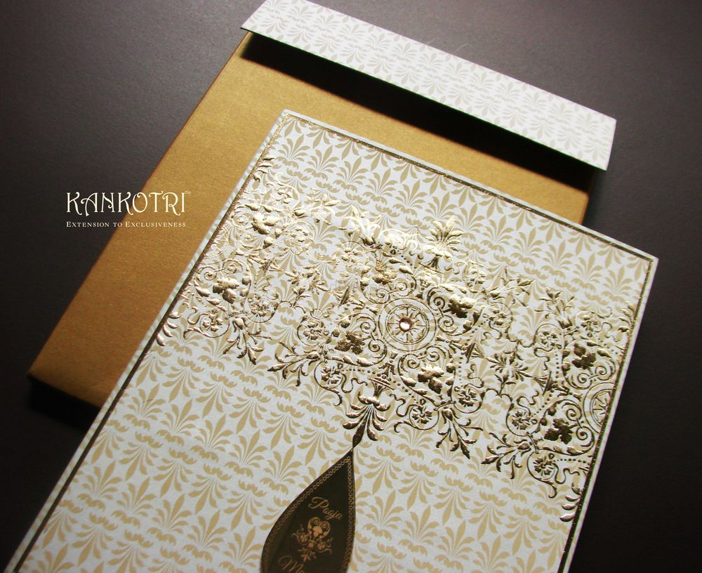 Photo of white and gold invitations