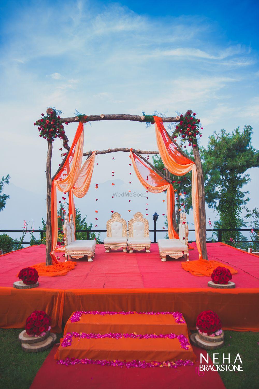 Photo of Orange mandap with sticks and drapes
