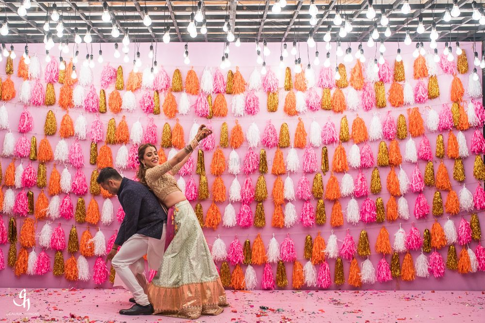 Photo of Bright and colorful tassel stage decor for mehendi or sangeet