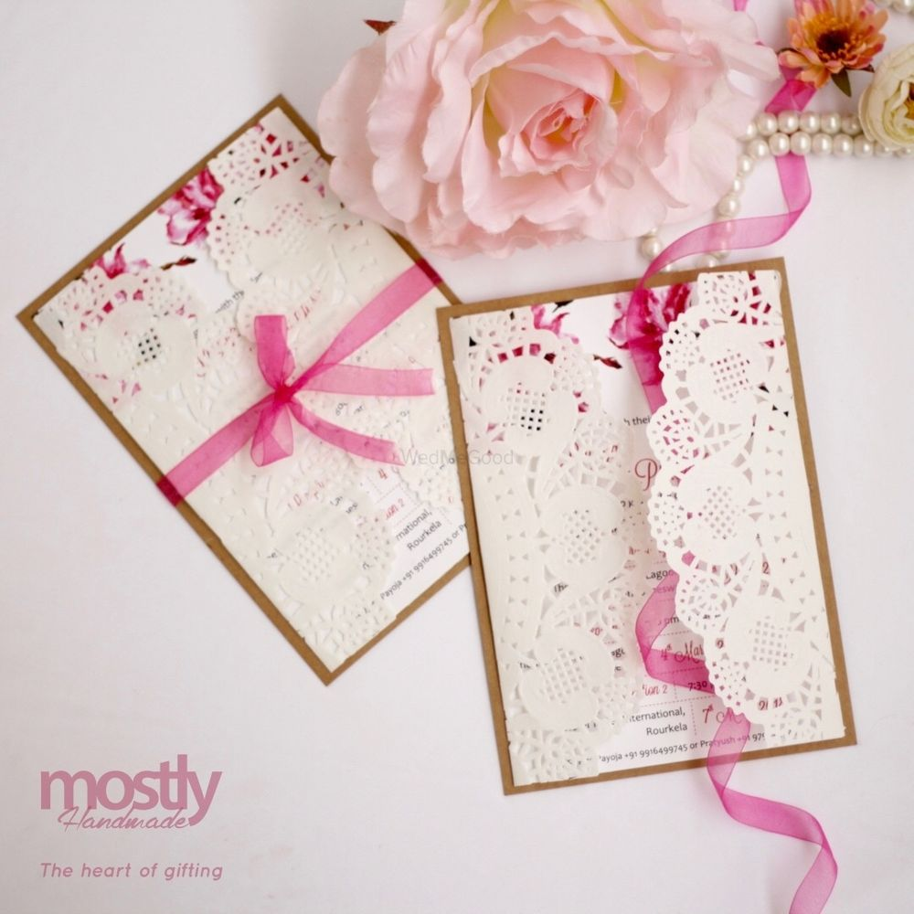 Photo of White and pink laser cut wedding cards