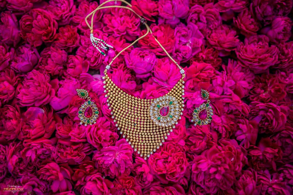 Photo of Bridal necklace and earrings with floral backdrop