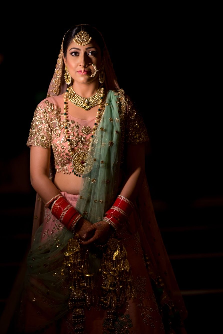 Photo of Pastel bridal lehenga portait in dark