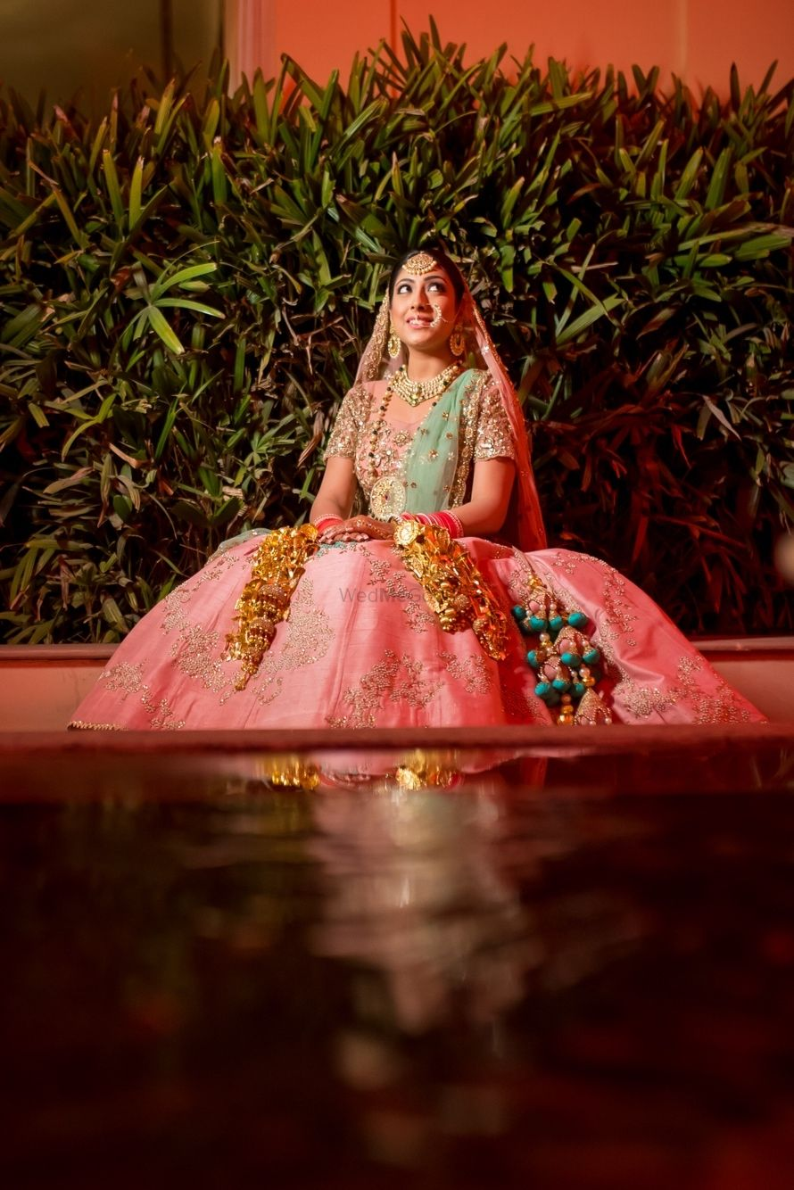 Photo of Light pink and green lehenga with contrasting tassels