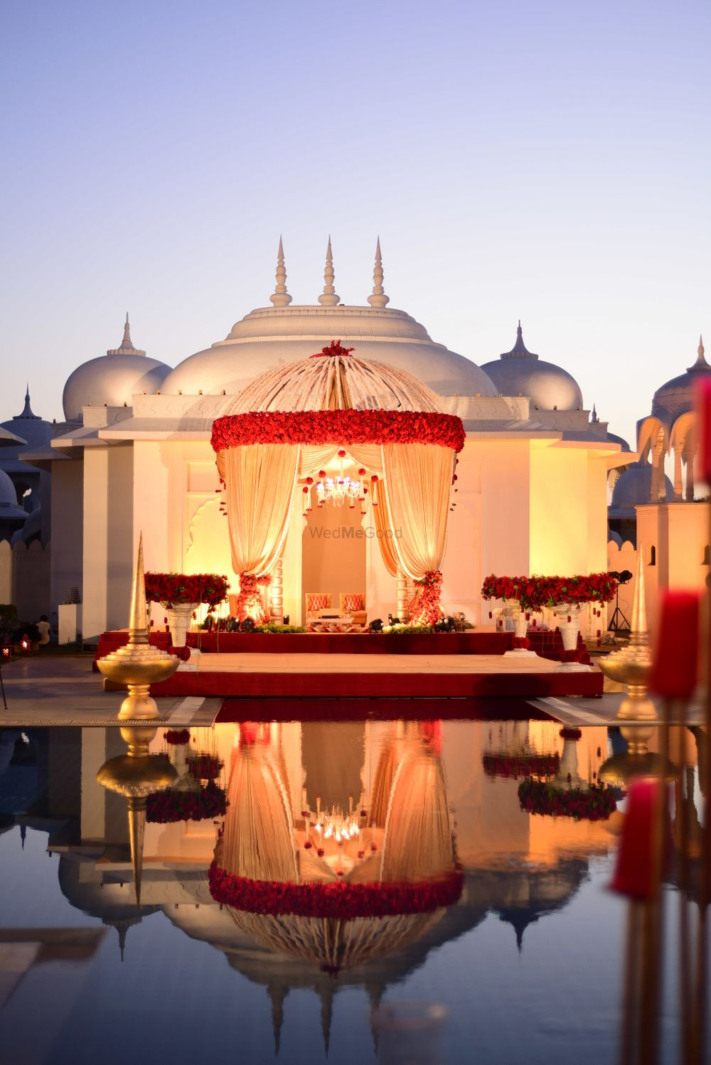 Photo of Well lit mandap in red and gold by the water