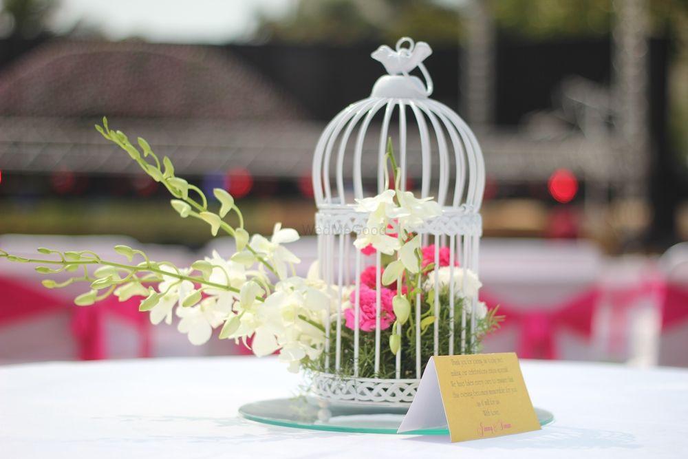 Photo of birdcage with floral arrangements