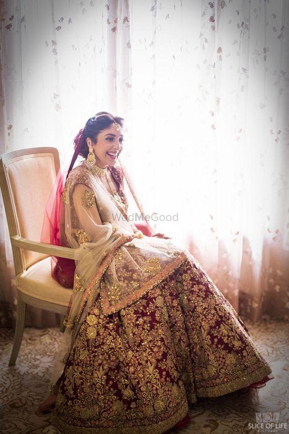 Photo of Winter wedding maroon and gold bridal lehenga