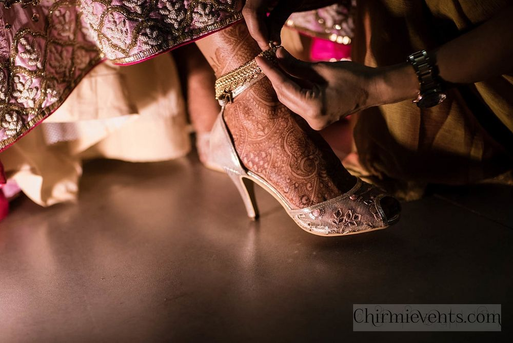 Photo of Bridesmaid tying anklet to bride with pink shoes