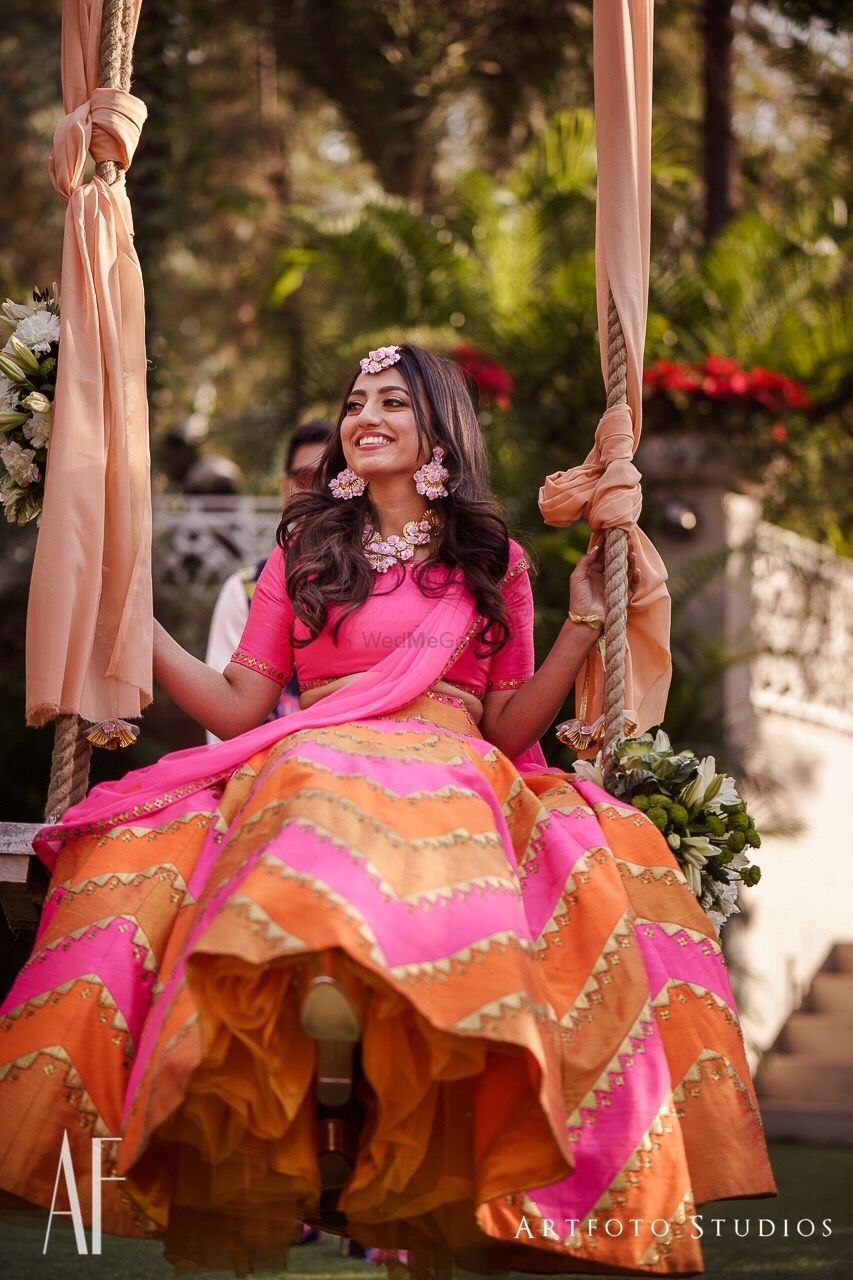 Photo of Mehendi day bridal portrait with bride on swing