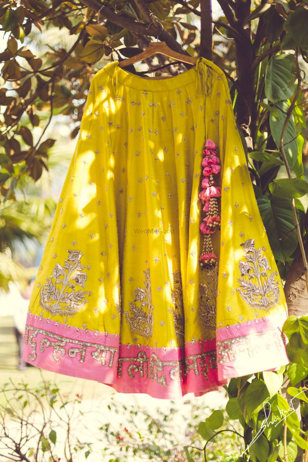 Photo of Fun wedding lehenga in yellow with a pink border and personalised quotes on the border