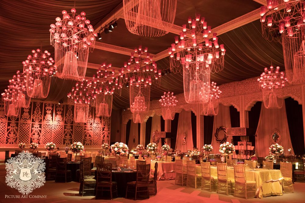 Photo of Multiple chandeliers for a wedding function lit by candles