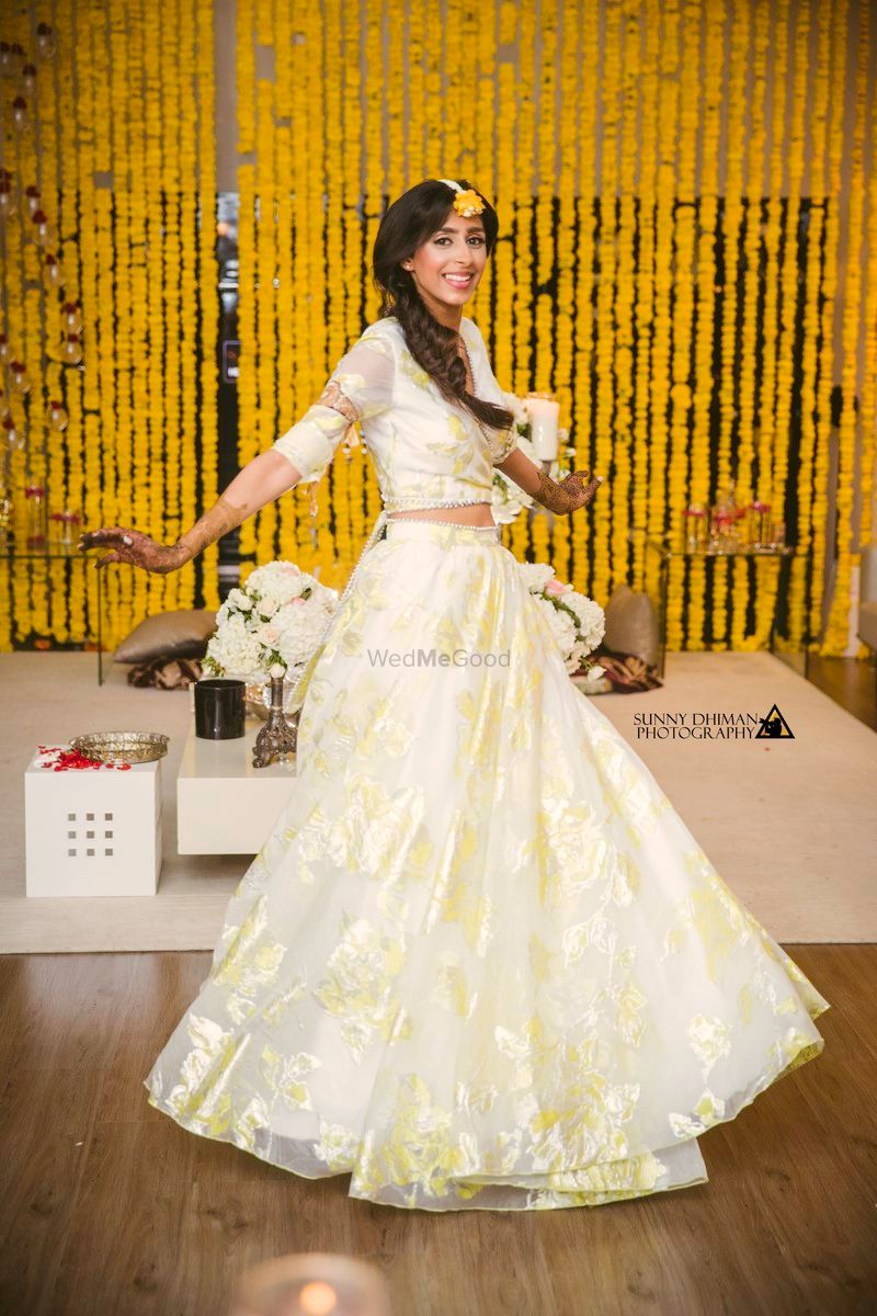 Photo of Bride twirling in simple off white organza lehenga