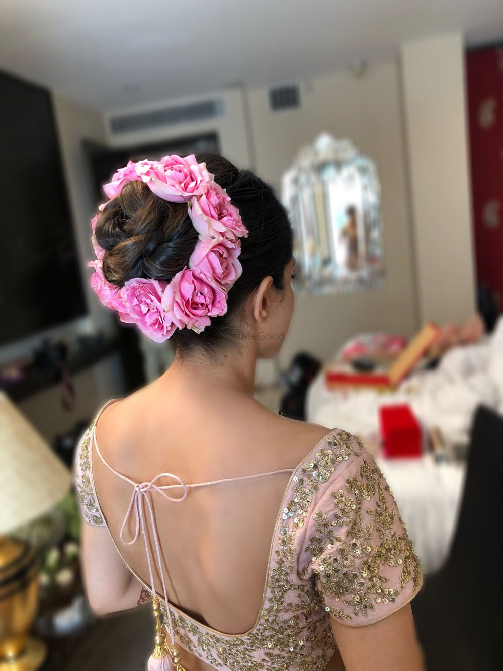 Photo of Bridal bun with pink roses on the edge