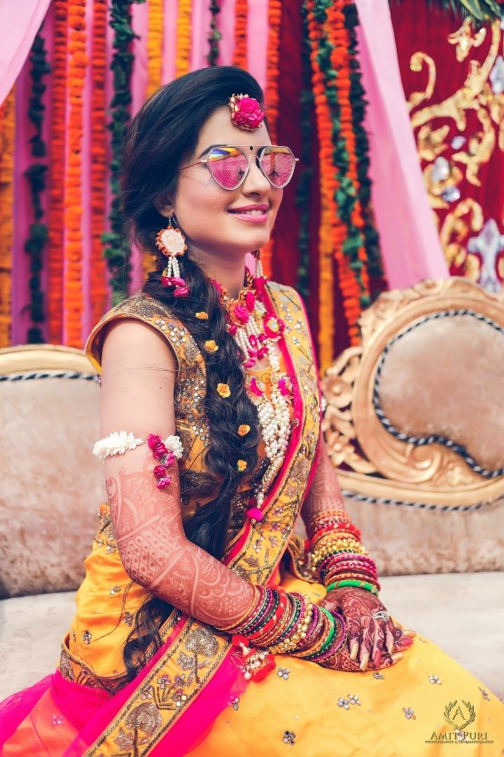 Photo of Bride in contrasting floral and gota jewellery on mehendi