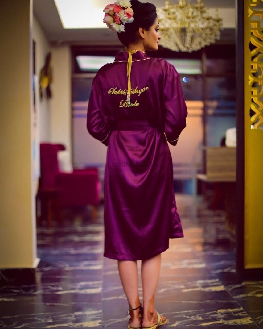 Photo of Getting ready shot with bride in wine coloured robe