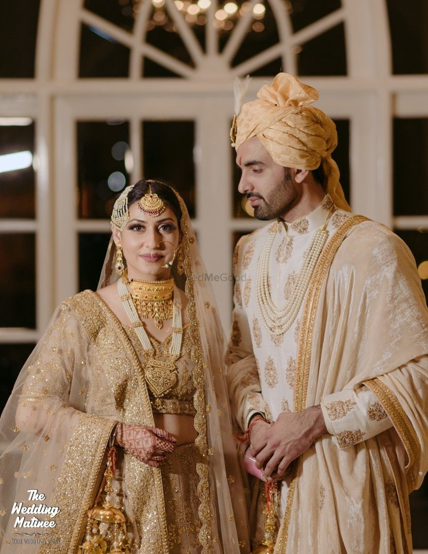 Photo of Matching bride and groom in ivory and gold outfits