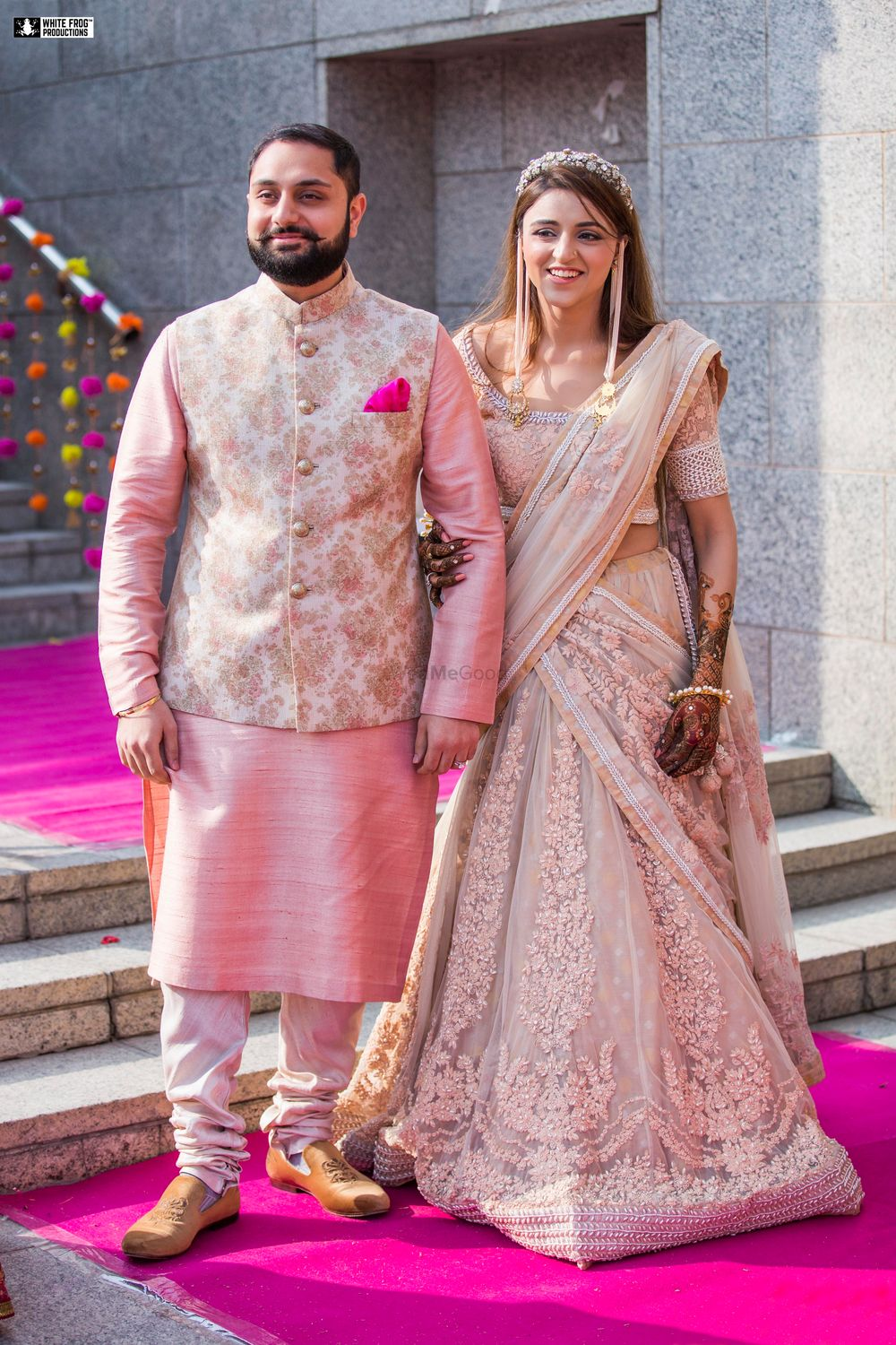 Photo of Matching bride and groom on mehendi in pastels
