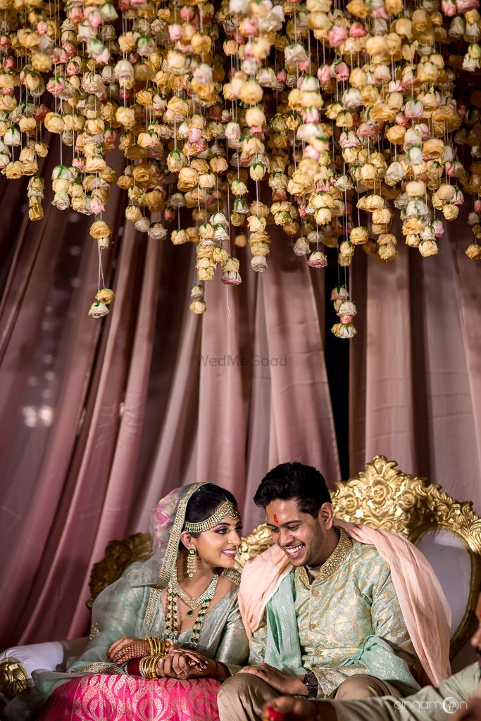 Photo of Matching bride and groom under floral string mandap