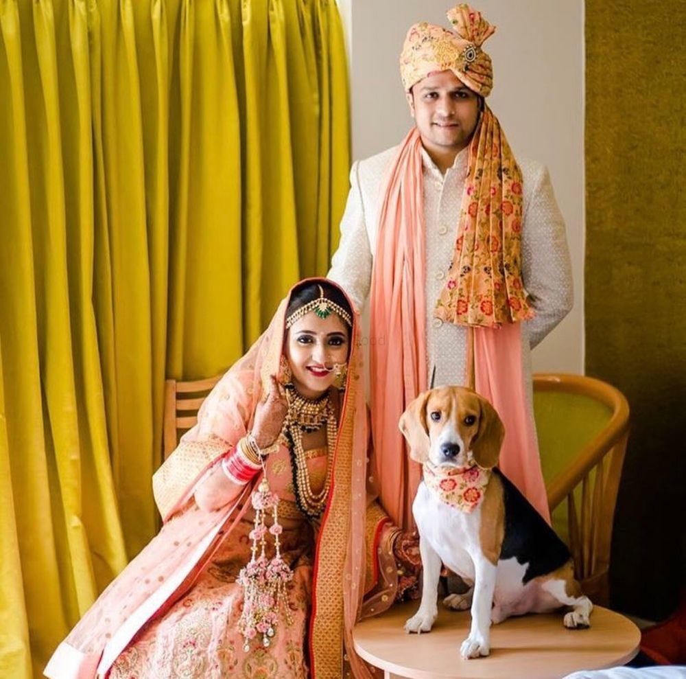 Photo of A bride and groom in coordinated outfits pose with a dog