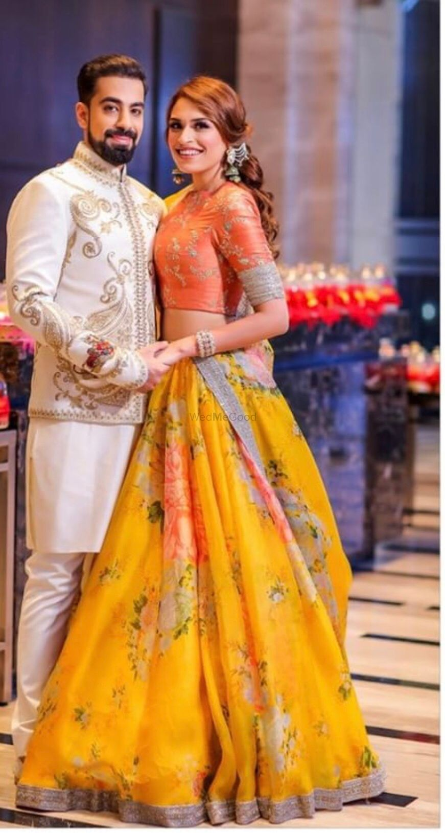 Photo of A bride and groom pose on their mehendi day