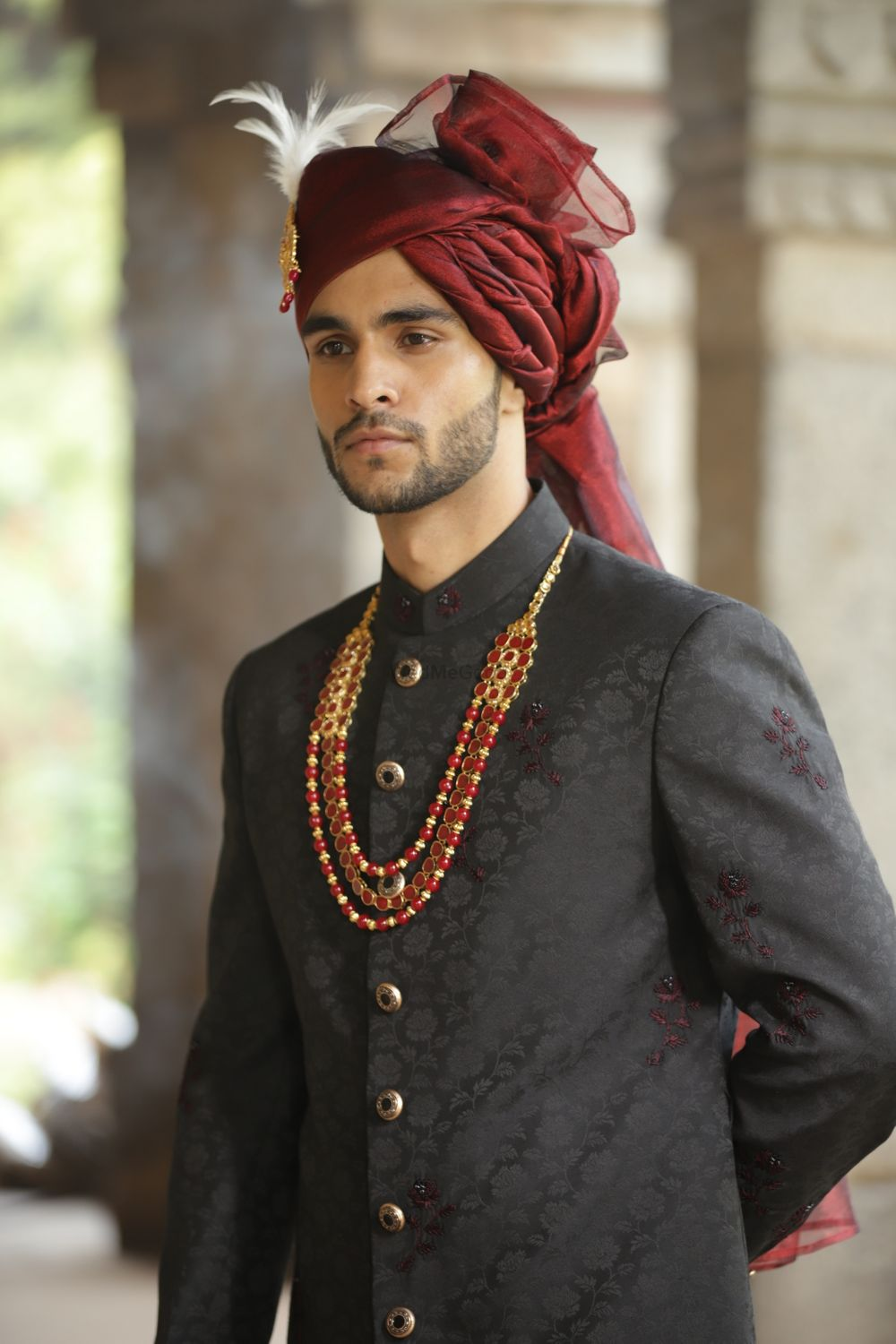 Photo of Groom in embroidered black sherwani and deep red safa.