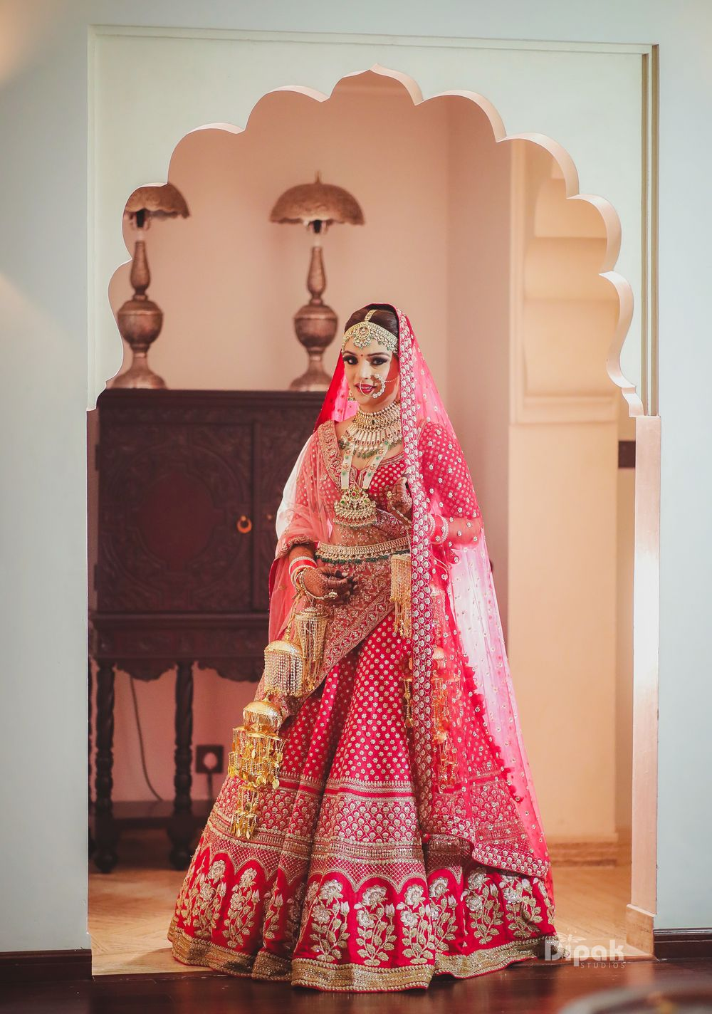 Photo of Bride in red and gold bridal lehenga with floral motifs