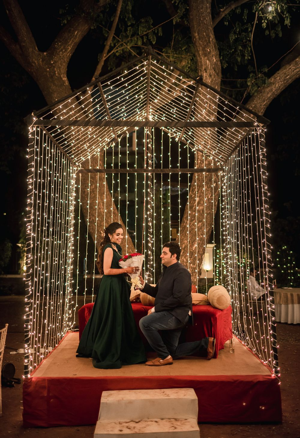 Photo of a groom to be goes down on one knee for his bride to be at their sangeet ceremony