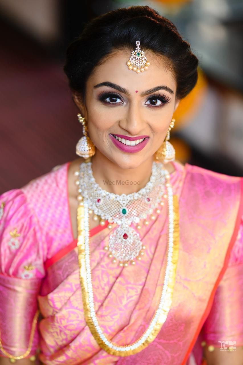 Photo of south indian bridal jewellery with layered necklaces and pink saree