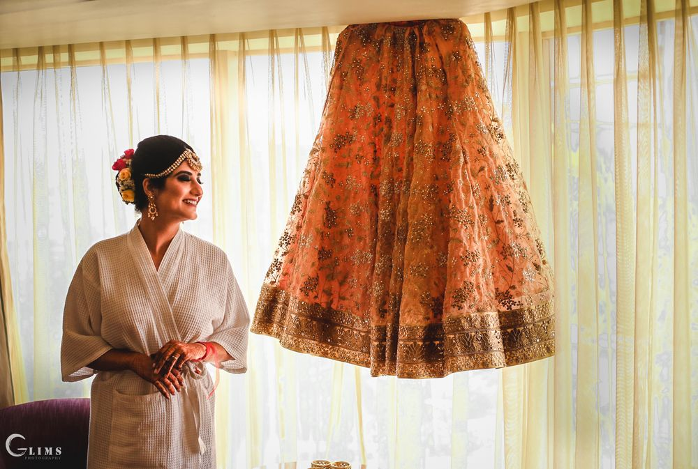 Photo of Bride with lehenga on the hanger while getting ready