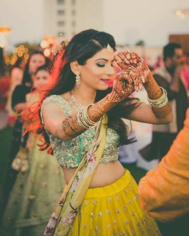 Photo of Bride on mehendi dancing in yellow lehenga