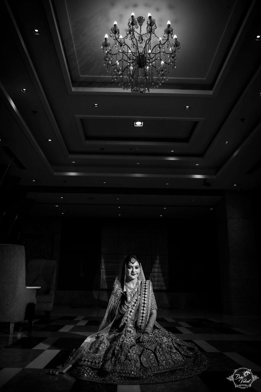 Photo of Timeless black and white bridal portrait under chandelier