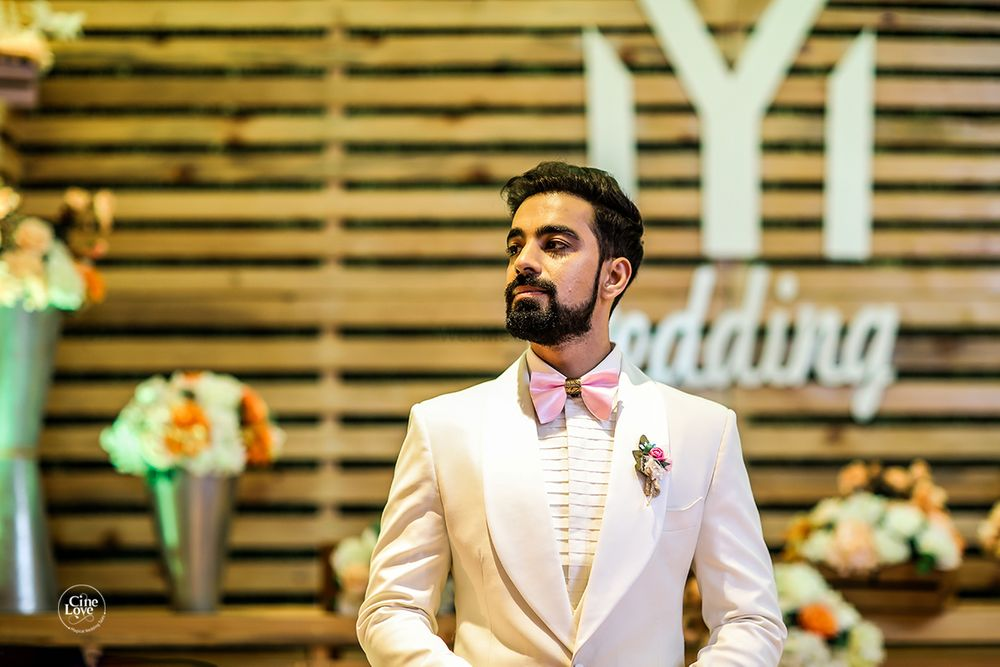 Photo of Quirky groom with light pink bow tie white suit