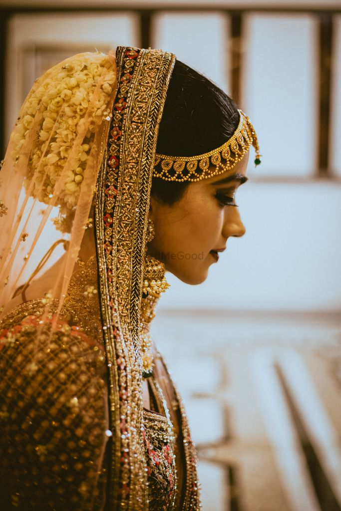 Photo of Bridal bun with florals and dupatta over it