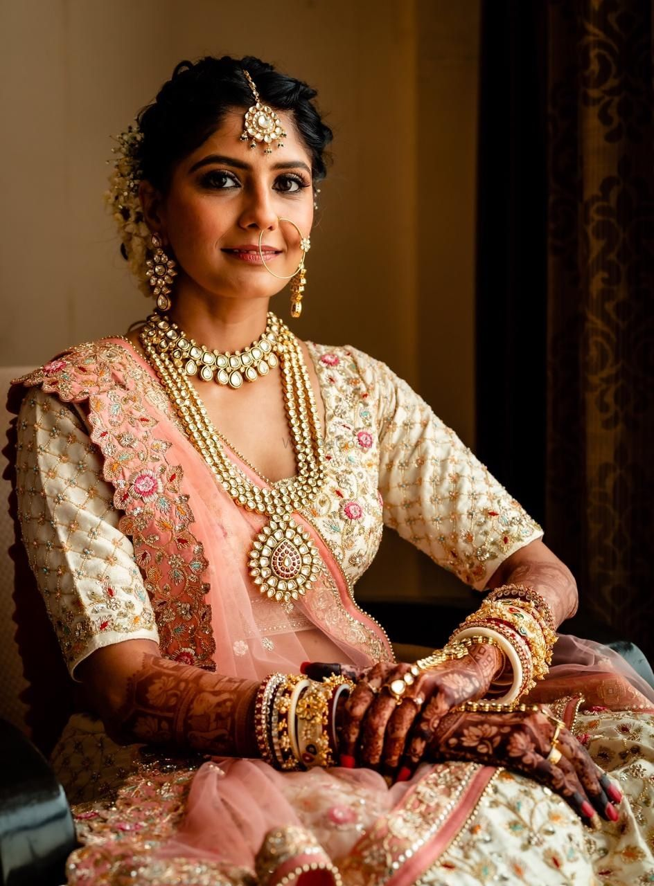 Photo of Bride wearing a white and pink lehenga.