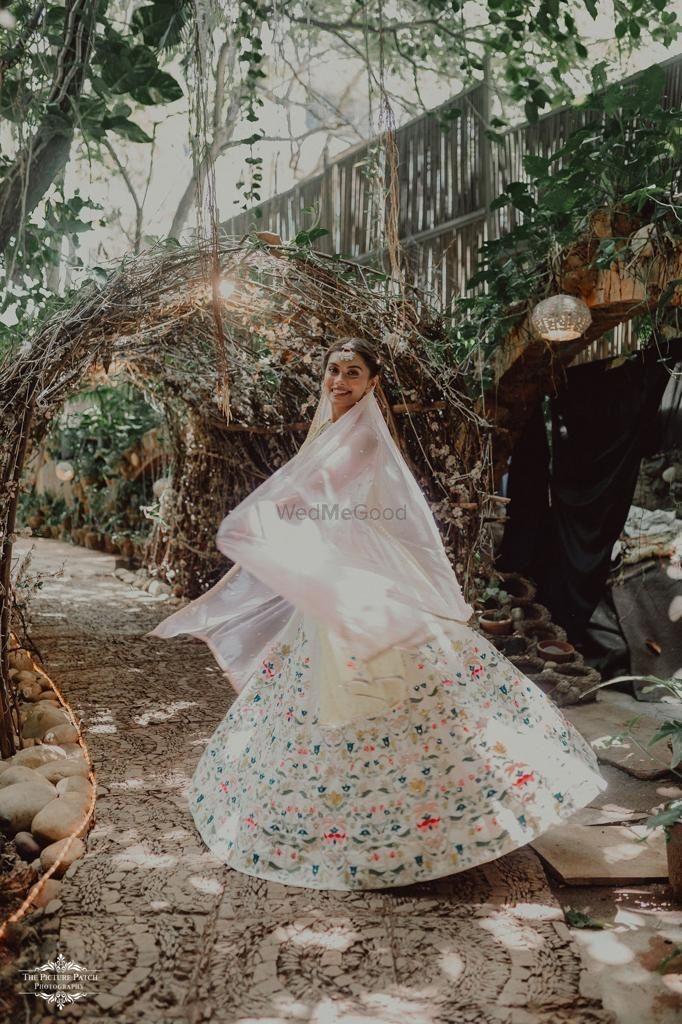 Photo of Bride twirling around in her ivory lehenga.
