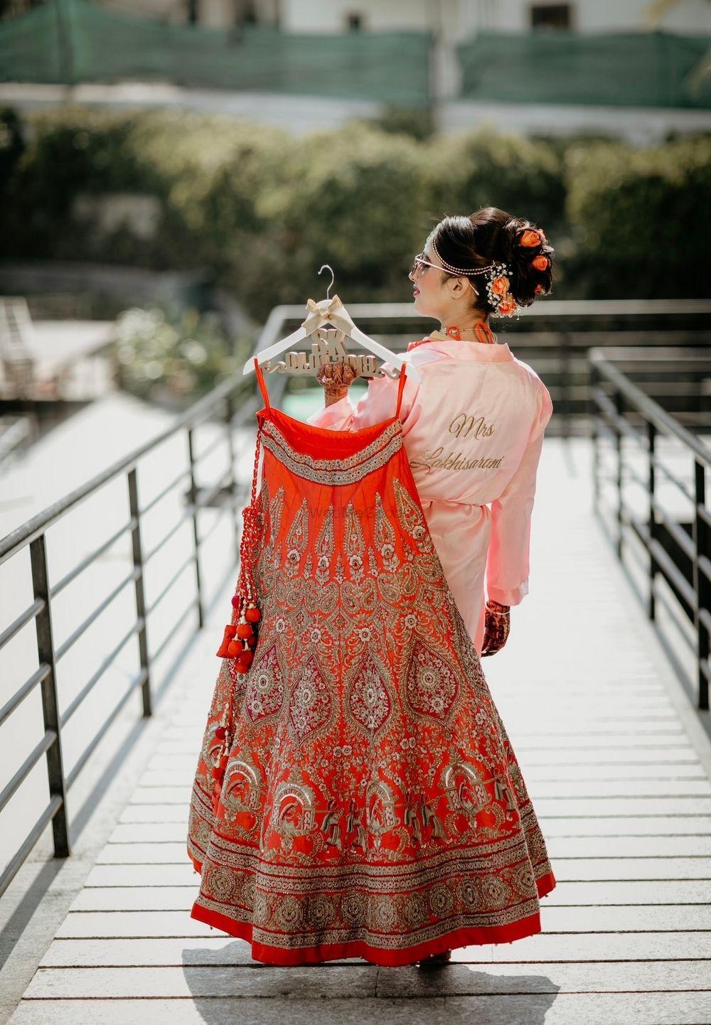 Photo of Outdoor bridal shoot holding lehenga