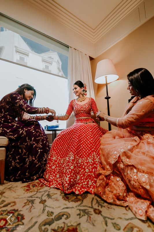 Photo of Bride with bridesmaids helping her get ready