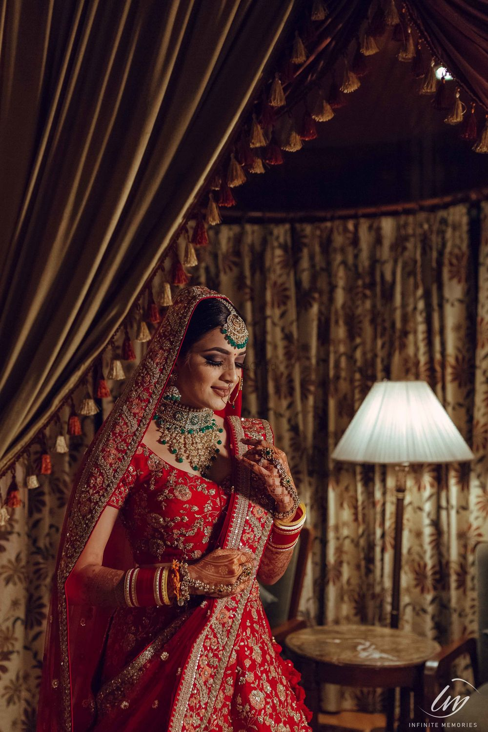 Photo of Bridal portrait in room in red lehenga and green jewellery